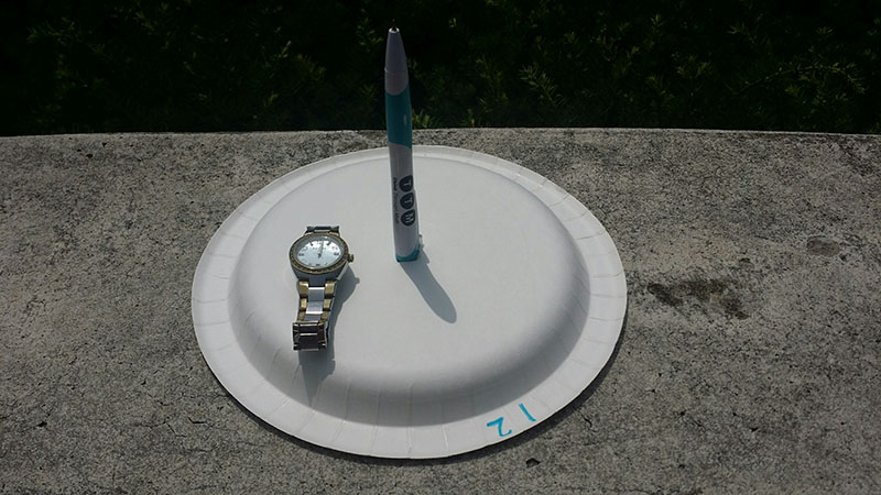 homemade sundial with watch
